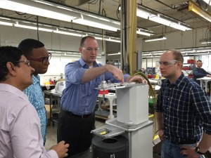Parr's Tim Lehman describing the belt and pulley mechanism on a stirred reactor with Farid Ali, Neurin Rodriguez Romero, and Rafal Kuran